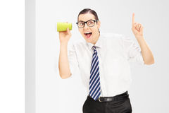 Smiling man with glasses listening through the wall with a cup Royalty Free Stock Image