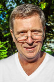 Smiling man with glasses outside in the sun Royalty Free Stock Photo