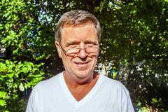 Smiling man with glasses outside in the sun Royalty Free Stock Image