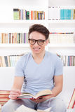 Smiling man with glasses reading a book on the couch Stock Images