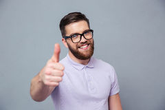 Smiling man in glasses showing thumb up Stock Images