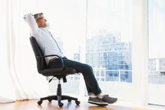 Smiling man with glasses sitting on office chair and relaxing Stock Photo