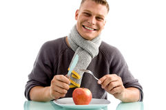 Smiling man going to eat apple with fork and knife Stock Photos