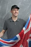 Smiling man in gray against background of British flag Stock Images