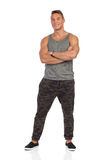 Smiling Man In Gray Tank Top Full Length Isolated. Smiling young muscular man in pants with camo, gray tank top and black sneakers posing with arms crossed. Full Royalty Free Stock Photography