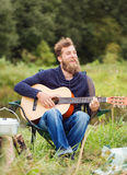 Smiling man with guitar and dixie in camping Royalty Free Stock Photo