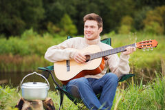 Smiling man with guitar and dixie in camping Stock Photography