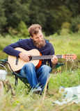 Smiling man with guitar and dixie in camping Stock Photo