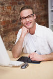 Smiling man with hand on chin drawing on graphic tablet Stock Photos