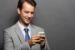 A smiling man with a handphone isolated. A potrait of a man which smiling over a handphone isolated Royalty Free Stock Image