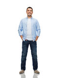 Smiling man with hands in pockets. Happiness and people concept - smiling man with hands in pockets Royalty Free Stock Images