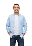 Smiling man with hands in pockets. Happiness and people concept - smiling man with hands in pockets Royalty Free Stock Image