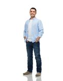 Smiling man with hands in pockets. Happiness and people concept - smiling man wearing shirt and jeans with hands in pockets Royalty Free Stock Photo