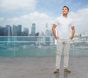 Smiling man with hands in pockets looking up Stock Image