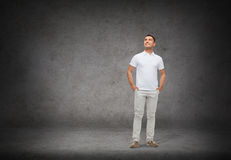Smiling man with hands in pockets looking up Royalty Free Stock Images