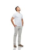 Smiling man with hands in pockets looking up Royalty Free Stock Image