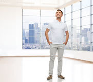 Smiling man with hands in pockets looking up Stock Images