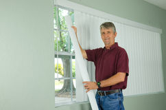 Smiling man hanging vertical blinds window treatment. A handy man home repair service technician or home owner hanging white vertical blinds for the window Stock Photo