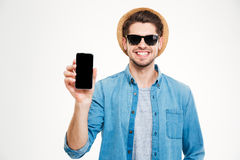 Smiling man in hat and sunglasses holding blank screen smartphone Royalty Free Stock Image