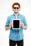 Smiling man in hat and sunglasses holding blank screen tablet Royalty Free Stock Photos