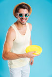 Smiling man in hat and sunglasses playing with frisbee disk Stock Photography