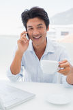 Smiling man having coffee and talking on phone Stock Photography