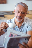 Smiling man having cup of coffee reading newspaper Royalty Free Stock Images