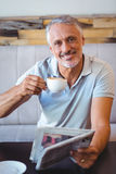 Smiling man having cup of coffee reading newspaper Royalty Free Stock Image