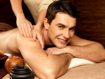 Smiling man having massage in the spa salon Stock Image