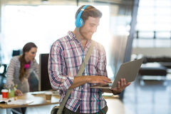 Smiling man with headphone using laptop stock image