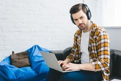Smiling man in headphones working on laptop. In light office stock image