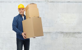 Smiling man in helmet with cardboard boxes Stock Image