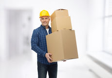 Smiling man in helmet with cardboard boxes Stock Photography