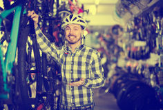Smiling man in helmet chooses for himself sports bike in bicycle Stock Photography