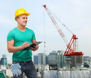Smiling man in helmet with clipboard Stock Image
