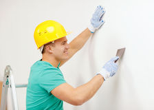 Smiling man in helmet doing renovations at home. Repair, renovation and home concept - smiling man in helmet doing renovations at home royalty free stock images