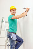 Smiling man in helmet hammering nail in wall. Reapir, building and home renovation concept - smiling man in yellow protective helmet hammering nail in wall Stock Images