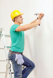 Smiling man in helmet hammering nail in wall. Reapir, building and home renovation concept - smiling man in yellow protective helmet hammering nail in wall Royalty Free Stock Photos