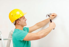 Smiling man in helmet hammering nail in wall Royalty Free Stock Image