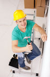 Smiling man in helmet hammering nail in wall. Repair, building and home renovation concept - smiling man in yellow protective helmet hammering nail in wall Stock Image