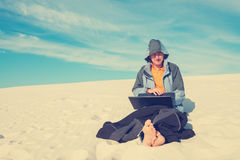 Smiling man hiker, sitting with a laptop in desert Royalty Free Stock Photo