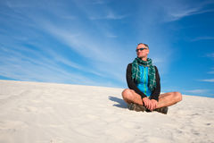 Smiling man hiker sitting and relaxing in the desert Royalty Free Stock Photo
