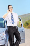 Smiling man on his automobile drinking coffee and talking on a p Stock Photography
