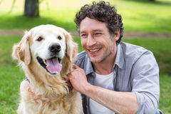Smiling man with his dog in park Royalty Free Stock Photos