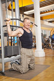 Smiling man in his forties exercising in gym. A smiling man in his forties exercising in a fitness studio training his latissimus and looking into camera Royalty Free Stock Photo