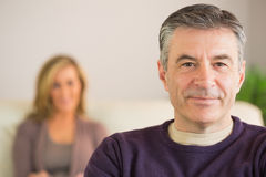 Smiling man with his wife in the background Stock Image