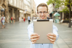 Smiling man hold tablet computer on urban street Royalty Free Stock Photo