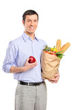 Smiling man holding an apple and bag Royalty Free Stock Photos
