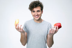 Smiling man holding apple and donut Royalty Free Stock Photography
