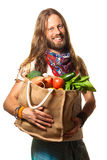 Smiling man holding a bag of fruit and vegetables. Smiling and healthy man holding a bag of fresh, organic fruit and vegetables looking into the camera Royalty Free Stock Photography